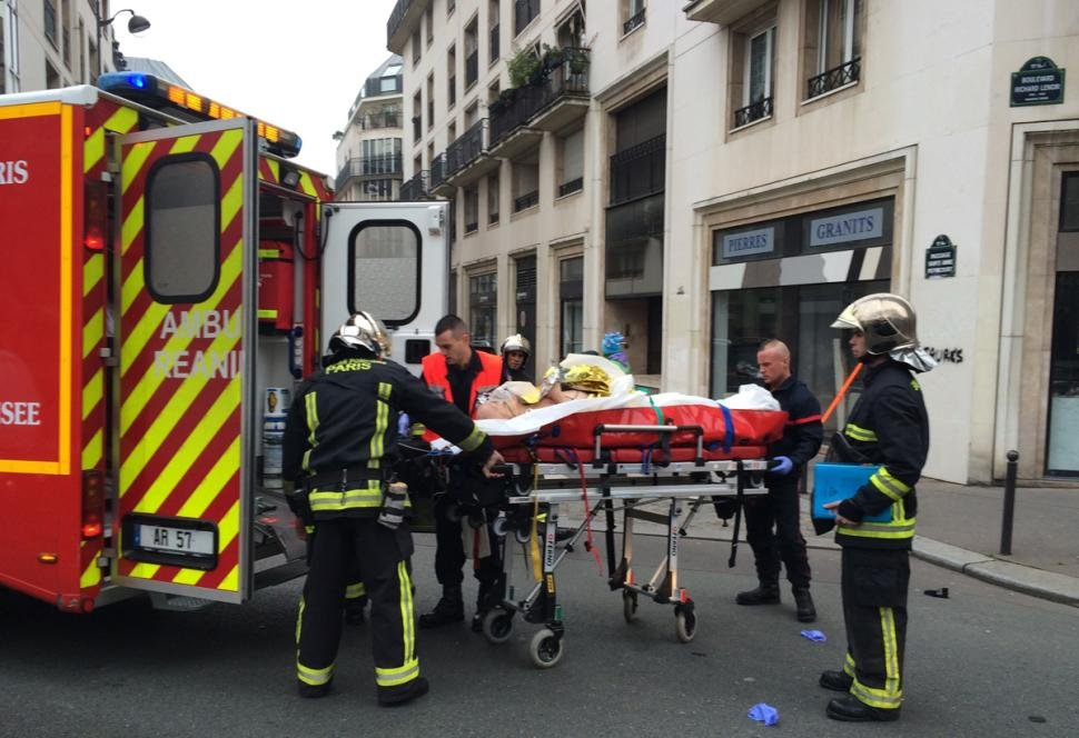 Firefighters carry an injured man on a stretcher in front of the offices of the French satirical newspaper Charlie Hebdo in Paris after armed gunmen stormed the offices. [Philippe Dupeyrat/AFP/Getty Images]